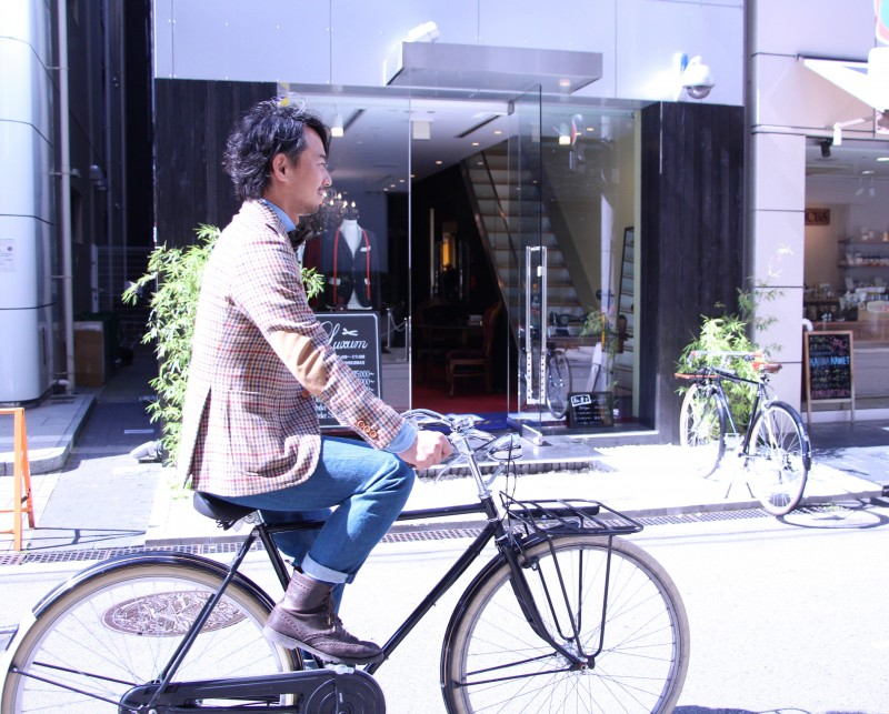 ツイードジャケットを来て自転車に乗るLuxum代表フィッター
