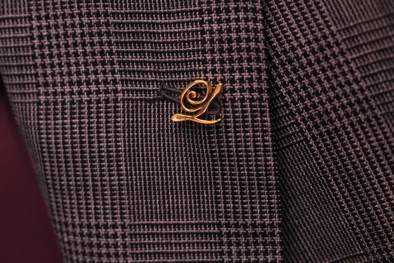 グレーのジャケットについているオーダーピンズの画像