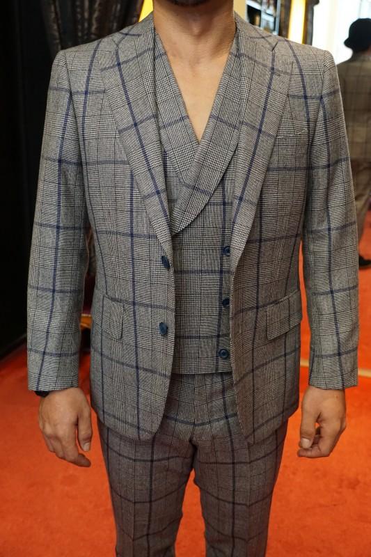グレーのグレンチェックに青のオーバーペンのスーツ